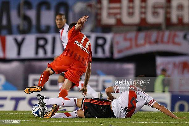 Matias Kranevitter of River Plate suffers an injury in his left foot as he fights for the ball with Federico Mancuello of Independiente a match...