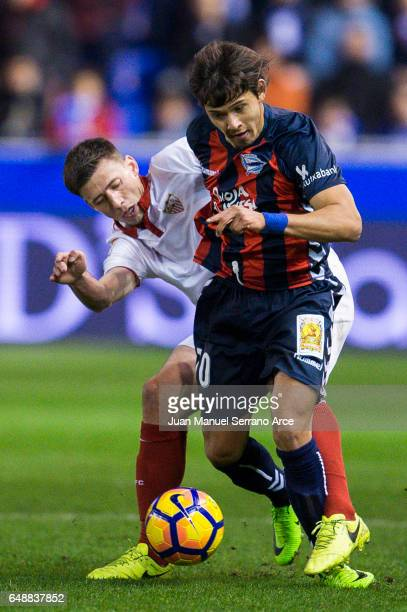 Matias Kranevitter of Sevilla FC duels for the ball with Oscar Romero of Deportivo Alaves during the La Liga match between Deportivo Alaves and...
