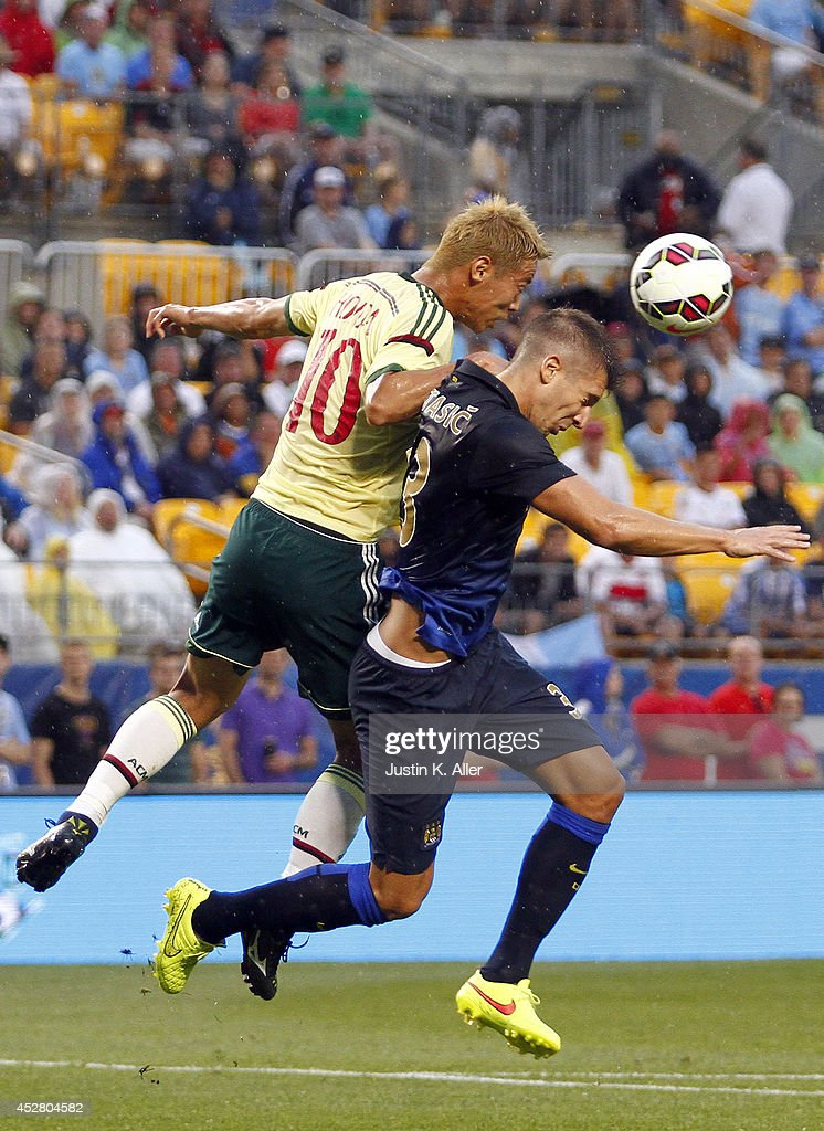 Matija NastasiÄ #33 of Manchester City heads a ball against <a gi-track='captionPersonalityLinkClicked' href=/galleries/search?phrase=Keisuke+Honda&family=editorial&specificpeople=2333022 ng-click='$event.stopPropagation()'>Keisuke Honda</a> #10 of AC Milan during International Champions Cup 2014 at Heinz Field on July 27, 2014 in Pittsburgh, Pennsylvania.