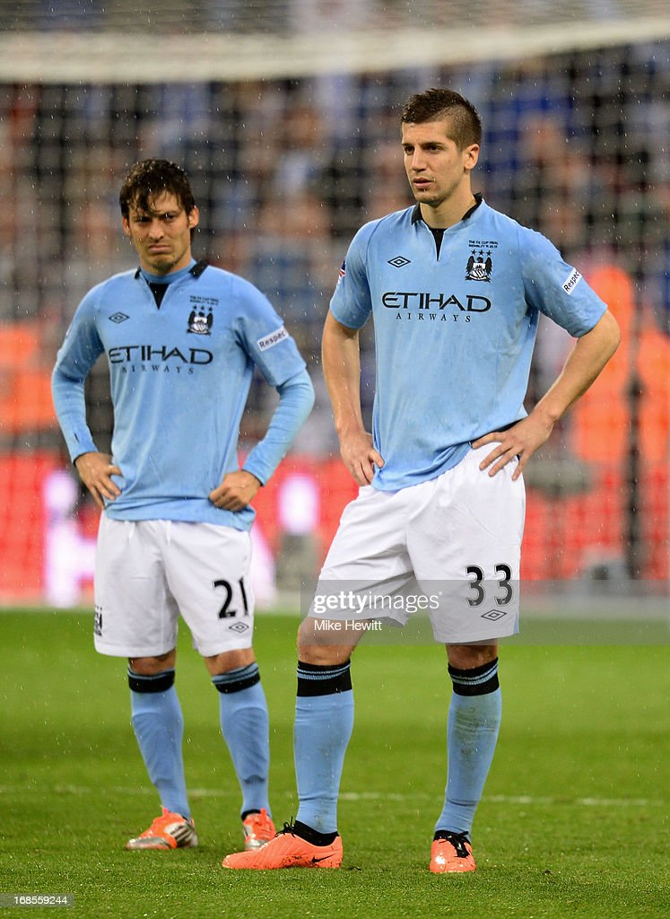 Matija Nastasic (33) and David Silva (21) of Manchester City look dejected in defeat after the FA Cup with Budweiser Final between Manchester City and Wigan Athletic at Wembley Stadium on May 11, 2013 in London, England.