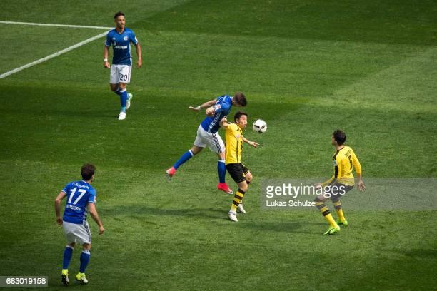 Matija Nastasic of Schalke attacks Shinji Kagawa of Dortmund during the Bundesliga match between FC Schalke 04 and Borussia Dortmund at VeltinsArena...