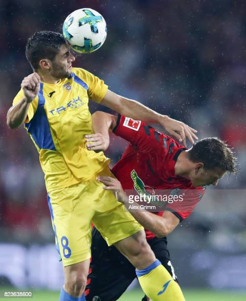 Matija Sirok of Domzale is challenged by Janik Haberer of Freiburg during the UEFA Europa League Third Qualifying Round first leg match between SC...