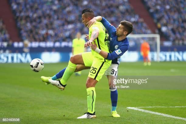 Matja Nastasic of Schalke battles for the ball with Raul Bobadilla of Augsburg during the Bundesliga match between FC Schalke 04 and FC Augsburg at...