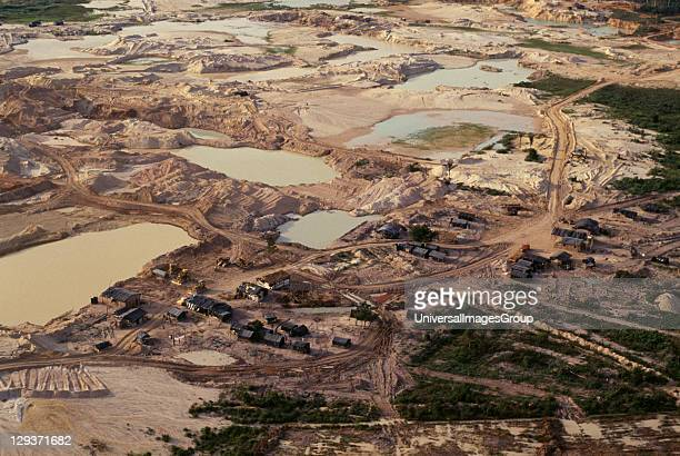 Mato Grosso Peixoto de Azevedo Gold mine on former Panara territory showing miners settlement and mercury washing pools deforestation and pollution...