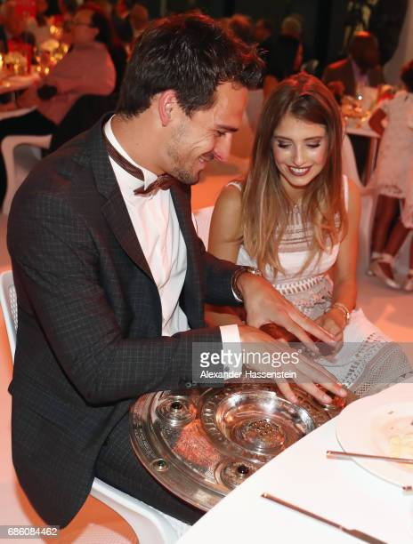 Mats Hummels and his wife Cathy Hummels hold the trophy during the FC Bayern Muenchen Championship party following the Bundesliga match between...