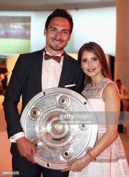Mats Hummels and his wife Cathy Hummels pose with the trophy during the FC Bayern Muenchen Championship party following the Bundesliga match between...