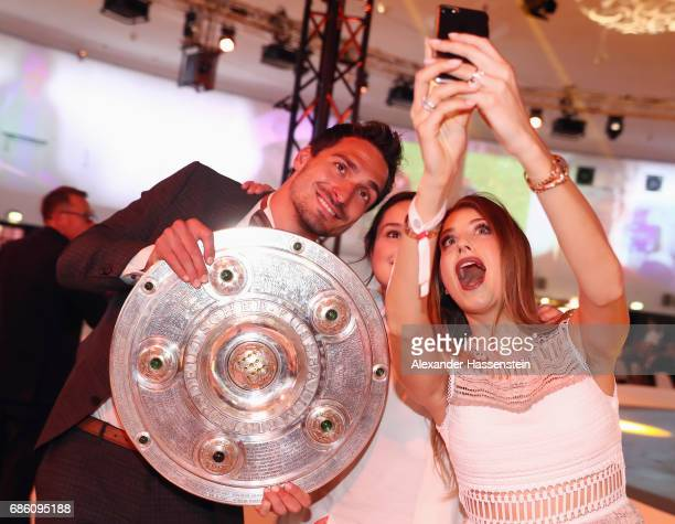 Mats Hummels and his wife Cathy Hummels take a selfie with the trophy during the FC Bayern Muenchen Championship party following the Bundesliga match...
