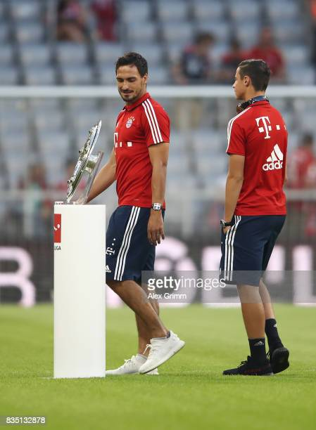 Mats Hummels and Marco Friedl of Bayern Munich walk past the championship trophy ahead of the Bundesliga match between FC Bayern Muenchen and Bayer...