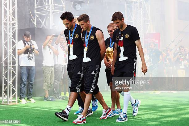 Mats Hummels Erik Durm Philipp Lahm and Thomas Mueller bring the World Cup trophy at the German team victory ceremony on July 15 2014 in Berlin...