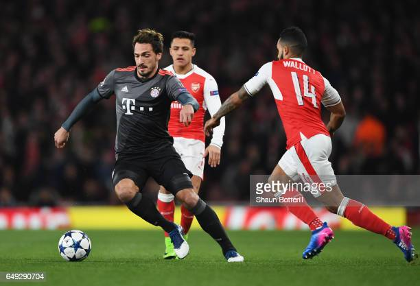 Mats Hummels of Bayern Muenchen evades Theo Walcott of Arsenal during the UEFA Champions League Round of 16 second leg match between Arsenal FC and...