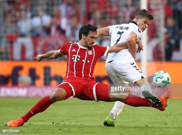 Mats Hummels of Bayern Muenchen fights for the ball with Florian Niederlechner of Freiburg during the Bundesliga match between FC Bayern Muenchen and...