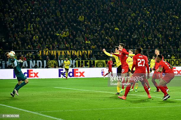 Mats Hummels of Borussia Dortmund beats goalkeeper Simon Mignolet of Liverpool to score their first goal during the UEFA Europa League quarter final...