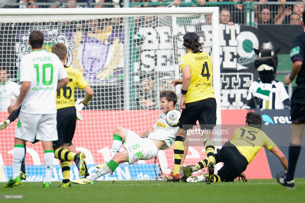 <a gi-track='captionPersonalityLinkClicked' href=/galleries/search?phrase=Mats+Hummels&family=editorial&specificpeople=595395 ng-click='$event.stopPropagation()'>Mats Hummels</a> of Borussia Dortmund challenges Havard Nordtveit of Borussia Moenchengladbach during the Bundesliga match between Borussia Moenchengladbach and Borussia Dortmund at Borussia-Park on October 5, 2013 in Moenchengladbach, Germany.