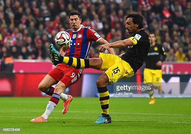 Mats Hummels of Borussia Dortmund controls the ball under pressure from Robert Lewandowski of Bayern Muenchen during the Bundesliga match between FC...