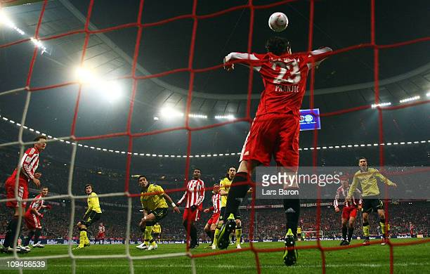 Mats Hummels of Dortmund heads his teams third goal over Danijel Pranjic of Muenchen during the Bundesliga match between FC Bayern Muenchen and...