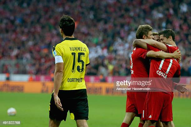 Mats Hummels of Dortmund looks dejected whilst Robert Lewandowski Thomas Mueller Douglas Costa and her team mates of Muenchen celebrate the 4th team...
