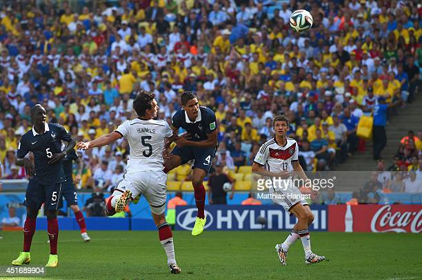 Mats Hummels of Germany scores his team's first goal against Raphael Varane of France during the 2014 FIFA World Cup Brazil Quarter Final match...