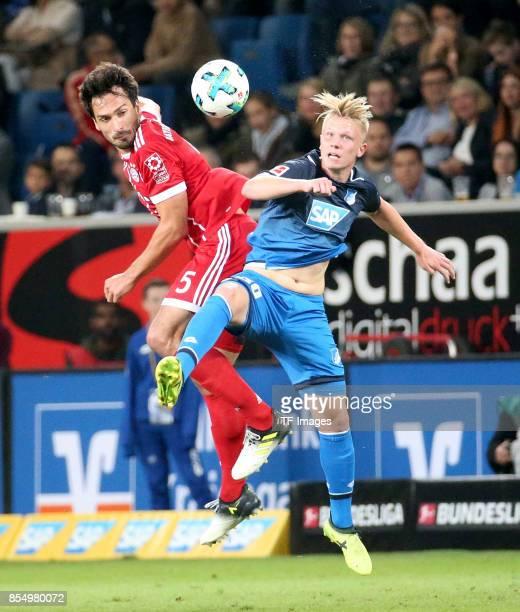 Mats Hummels of Muenchen and Dennis Geiger of Hoffenheim battle for the ball during the Bundesliga match between TSG 1899 Hoffenheim and FC Bayern...