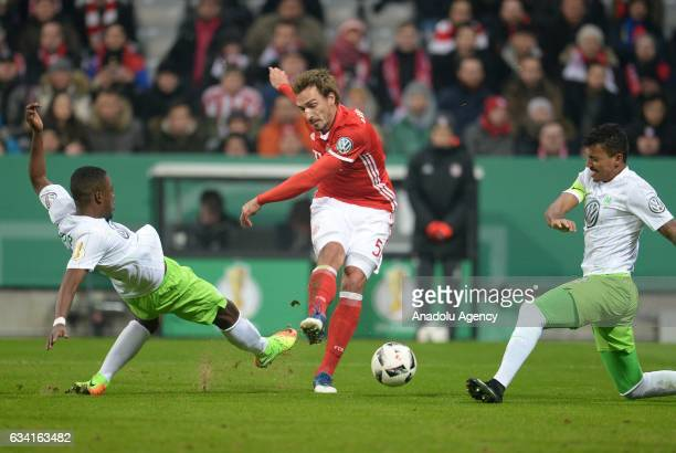 Mats Hummels of Munich and Riechedly Bazoer and Luiz Gustavo of Wolfsburg vie for the ball during the DFB Cup soccer match between FC Bayern Munich...