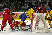 Mats Sundin of Sweden falls into the goal as Goalkeeper Tomas Vokoun of Czech Republic looks at the puck during the second period in the semi final...