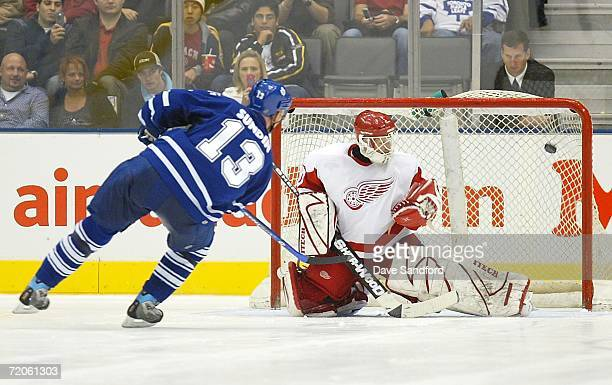Mats Sundin of the Toronto Maple Leafs puts a shot in past Chris Osgood of the Detroit Red Wings on the first attempt in the shootout during their...
