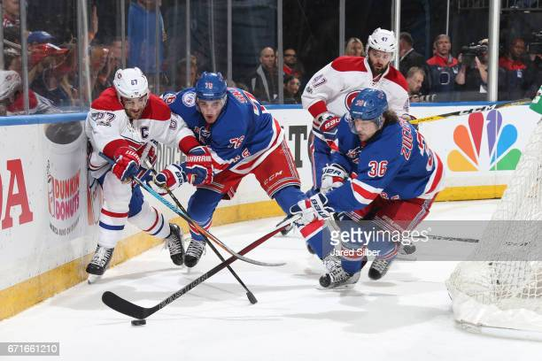 Mats Zuccarello and Brady Skjei of the New York Rangers battle for the puck against Max Pacioretty and Alexander Radulov of the Montreal Canadiens in...