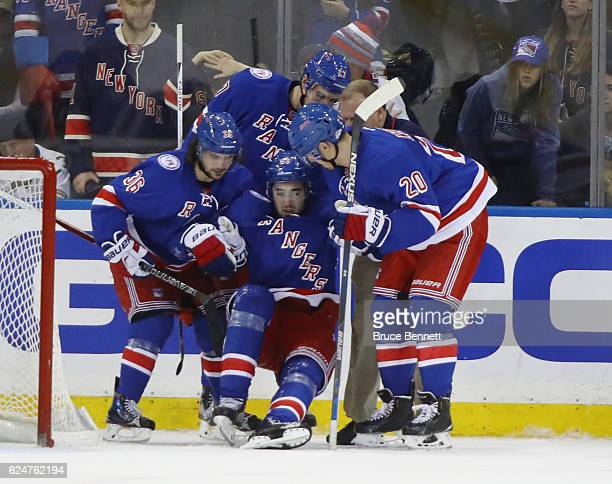Mats Zuccarello and Chris Kreider escourt Mika Zibanejad of the New York Rangers off the ice after his injury during the third period against the...