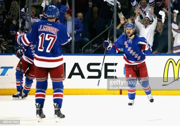 Mats Zuccarello and John Moore of the New York Rangers celebrate a goal by Benoit Pouliot of the New York Rangers on Jonathan Quick of the Los...