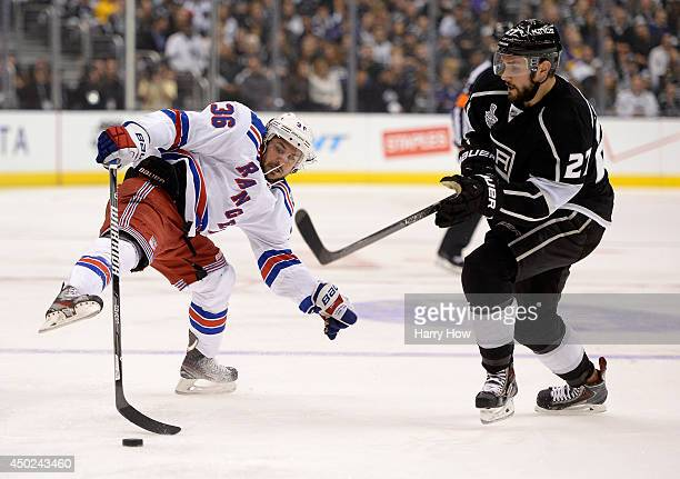 Mats Zuccarello of the New York Rangers and Alec Martinez of the Los Angeles Kings go after the puck in the first period during Game Two of the 2014...