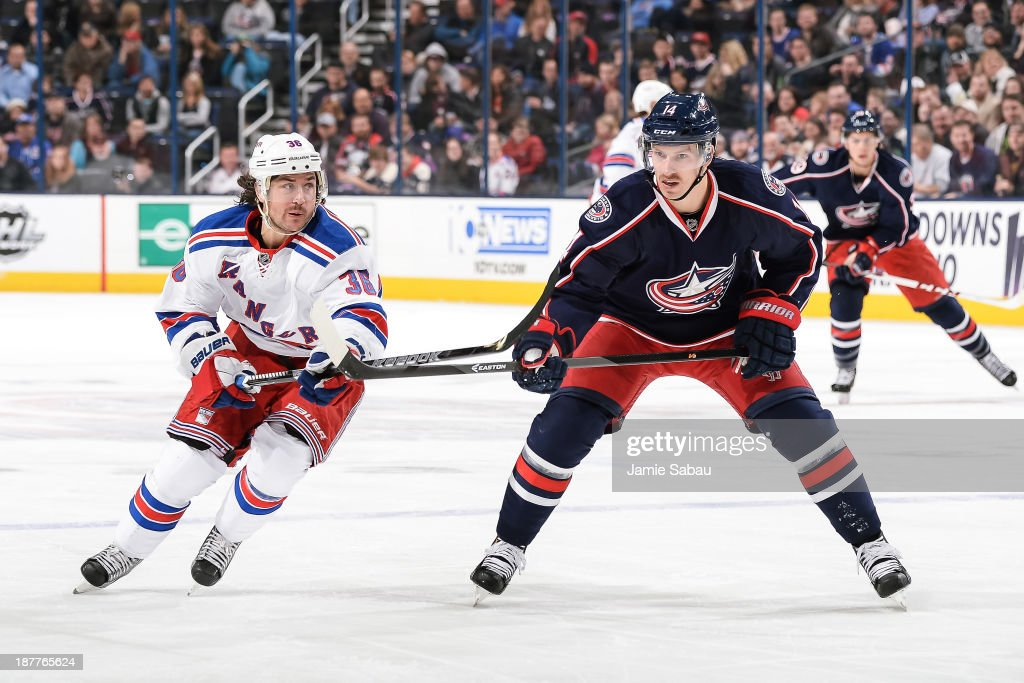 Mats Zuccarello #36 of the New York Rangers and Blake Comeau #14 of the Columbus Blue Jackets skate after a loose puck on November 7, 2013 at Nationwide Arena in Columbus, Ohio.