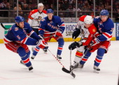 Mats Zuccarello of the New York Rangers and teammate Dan Girardi defeand against the shot from David Booth of the Florida Panthers on March 22 2011...