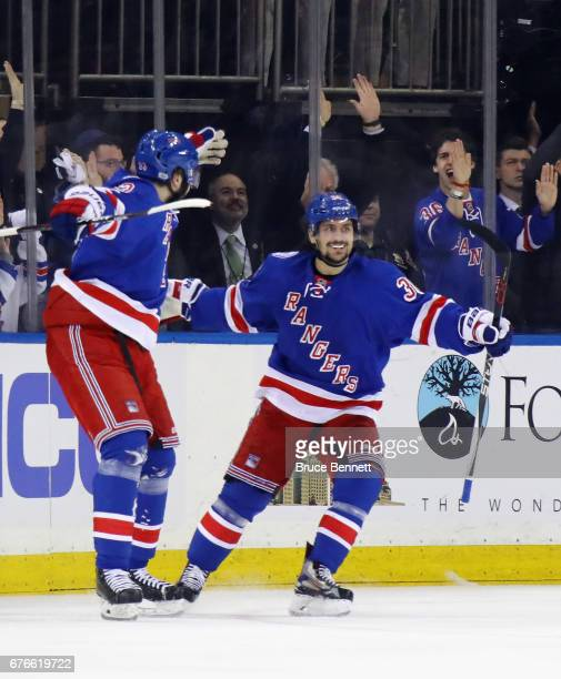 Mats Zuccarello of the New York Rangers celebrates his first period goal against the Ottawa Senators and is joined by Mika Zibanejad in Game Three of...