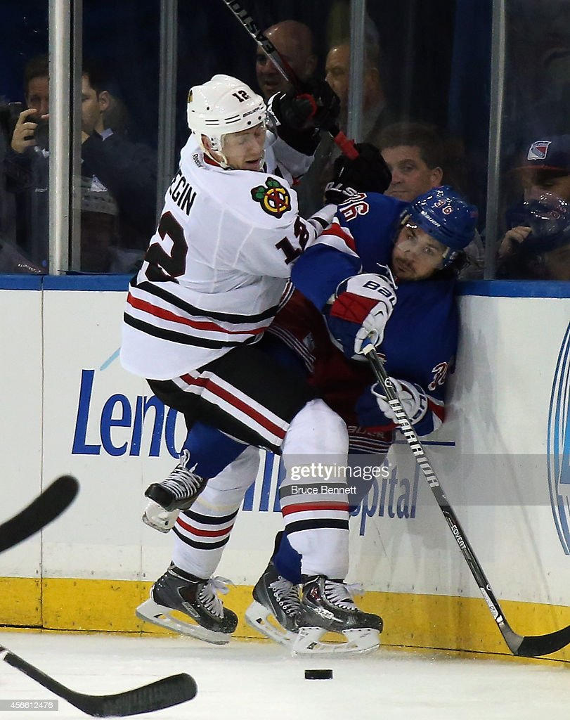 Mats Zuccarello #36 of the New York Rangers is hit into the boards by Peter Regin #12 of the Chicago Blackhawks at Madison Square Garden on October 3, 2014 in New York City. The Rangers defeated the Blackhawks 3-2 in the shootout.