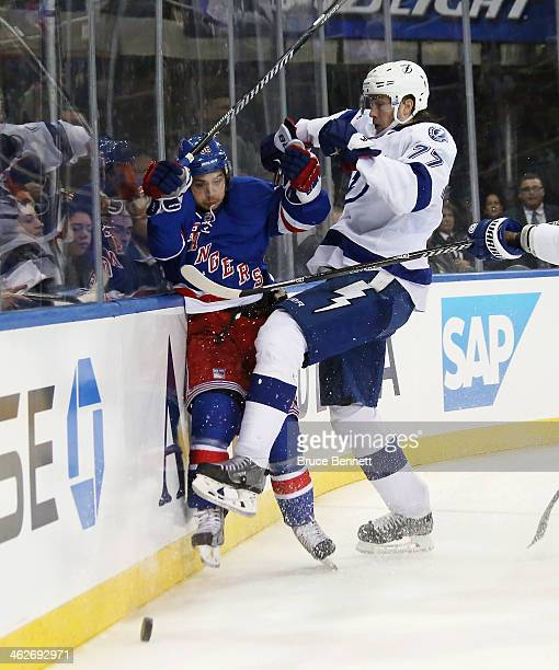 Mats Zuccarello of the New York Rangers is it into the boards by Victor Hedman of the Tampa Bay Lightning during the second period at Madison Square...