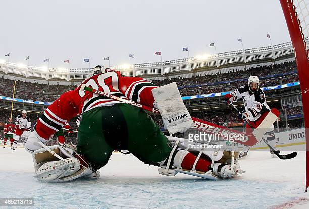 Mats Zuccarello of the New York Rangers scores a second period goal on Martin Brodeur of the New Jersey Devils during the 2014 Coors Light NHL...