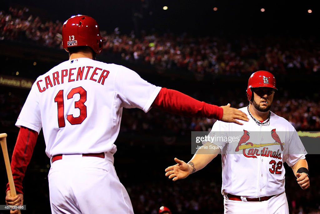 Matt Adams #32 celebrates with Matt Carpenter #13 of the St. Louis Cardinals after he scored on a single by Randal Grichuk #15 in the fourth inning against the San Francisco Giants during Game Two of the National League Championship Series at Busch Stadium on October 12, 2014 in St Louis, Missouri.