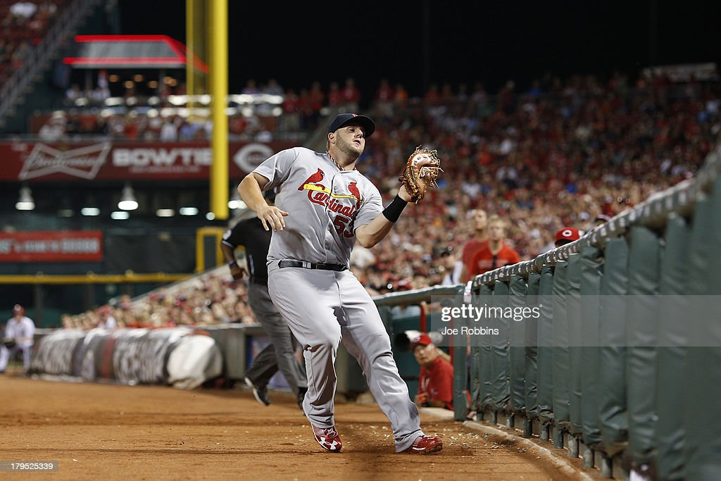 Matt Adams #53 of the St. Louis Cardinals catches a foul ball near the first base railing against the Cincinnati Reds during the game at Great American Ball Park on September 4, 2013 in Cincinnati, Ohio. The Cardinals won 5-4 in 16 innings.