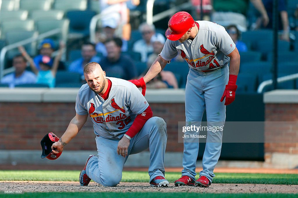 Matt Adams #32 of the St. Louis Cardinals reacts with teammate Jeremy Hazelbaker #41 after he was thrown at at home plate to end the fifth inning against the New York Mets at Citi Field on July 26, 2016 in the Flushing neighborhood of the Queens borough of New York City.