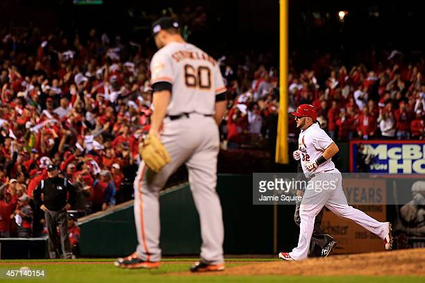 Matt Adams of the St Louis Cardinals rounds the bases on his solo home run in the eighth inning as Hunter Strickland of the San Francisco Giants...