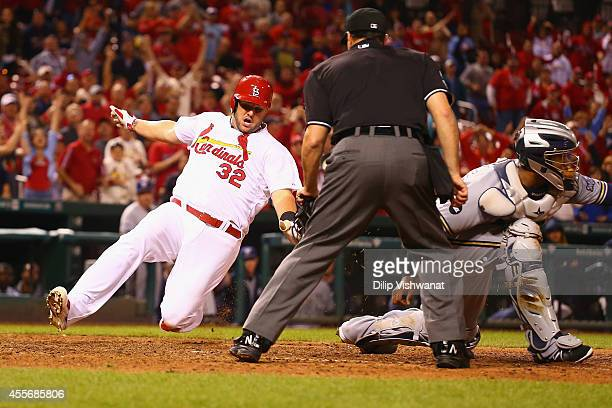 Matt Adams of the St Louis Cardinals scores the gamewinning run in the 13th inning against the Milwaukee Brewers at Busch Stadium on September 18...
