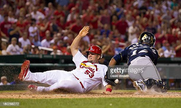 Matt Adams of the St Louis Cardinals slides past Martin Maldonado of the Milwaukee Brewers to score in the seventh inning at Busch Stadium on...