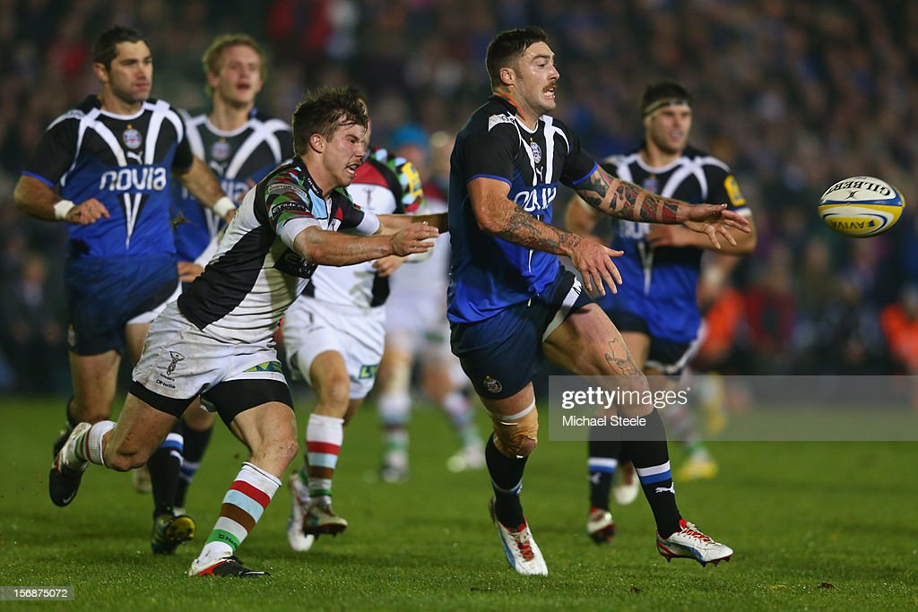 Matt Banahan (R) of Bath offloads as Sam Smith (L) of Harlequins closes in during the Aviva Premiership match between Bath and Harlequins at the Recreation Ground on November 23, 2012 in Bath, England.