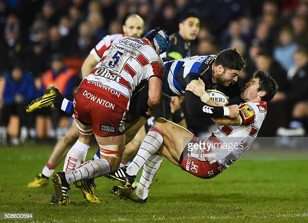 Matt Banahan of Bath Rugby is tackled by James Hook and Mariano Galarza of Gloucester Rugby during the Aviva Premiership match between Bath Rugby and...