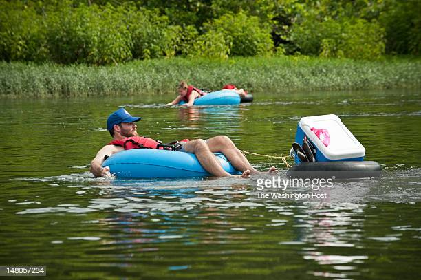 Harper's Ferry WV July 3Matt Barker of Winchester VA floats with a cooler in tow while tubing on the Potomac River in Harper's Ferry West Virginia on...