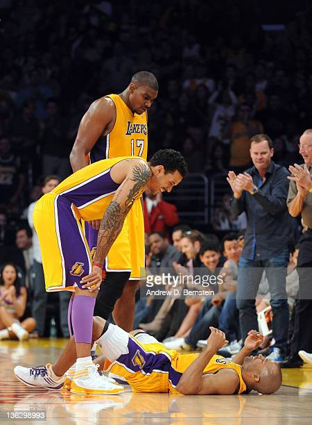 Matt Barnes and Andrew Bynum of the Los Angeles Lakers check on teammate Derek Fisher after Fisher dove for a loose ball during the game against the...
