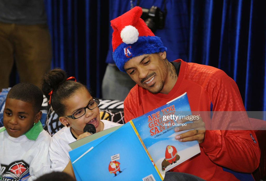 Matt Barnes #22 of the Los Angeles Clippers listens as a child reads from a book during the Clippers' 'Season of Giving' Adopt a Family event on December 20, 2012 at Salvation Army Seimon Family Youth & Community Center in Los Angeles, California.