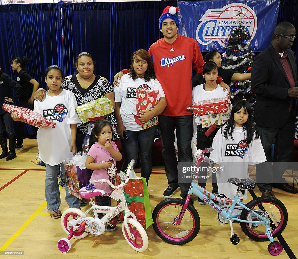 Matt Barnes #22 of the Los Angeles Clippers poses for a photo with the Lemus family during the Clippers' 'Season of Giving' Adopt a Family event on December 20, 2012 at Salvation Army Seimon Family Youth & Community Center in Los Angeles, California.