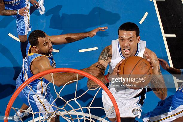 Matt Barnes of the Orlando Magic takes the ball to the basket against Malik Allen of the Denver Nuggets during the game on March 28 2010 at Amway...