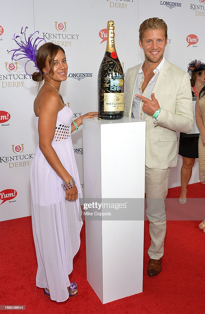 Matt Barr (R) and Heather Hemmens sign the Moet & Chandon 6L for the Churchill Downs Foundation during the 139th Kentucky Derby at Churchill Downs on May 4, 2013 in Louisville, Kentucky.