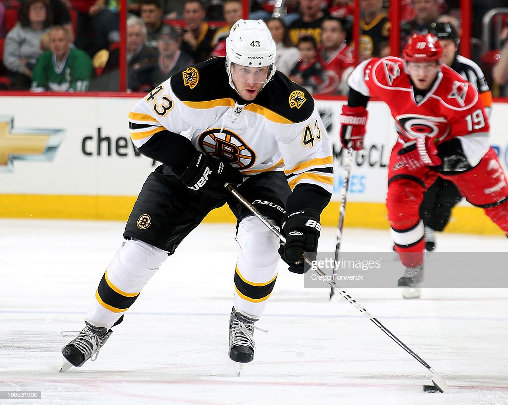 Matt Bartkowski #43 of the Boston Bruins carries through the neutral zone as Jiri Tlusty #19 of the Carolina Hurricanes looks on during their NHL game at PNC Arena on April 13, 2013 in Raleigh, North Carolina.